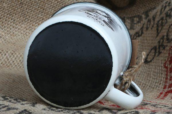 Der Carlos Kella Emaille-Becher im Retro-Look. Weißer Becher aus Emaille mit schwarzem Rand und einem Cars & Girls-Motiv auf der Vordeseite.