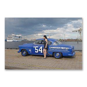 """Grossdruck """"Blue Rocket"""" auf Aludibond. Cars & Girls Fotografie von Carlos Kella im Format 150 x 100 cm mit Wandaufhängungen: Zombierella von den Messer Chups und ein Chevrolet Bel Air Hardtop Coupé von 1954"""