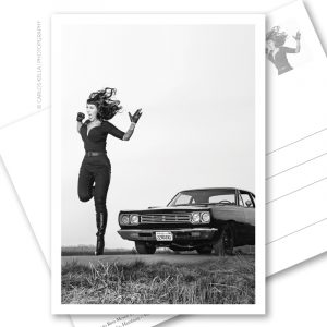 Postkarte Tura Satana Tribute. Ein postalischer Gruß im B-Movie-Style für US-Car- und Modern Pin-up Fans. Burlesque-Performer Lou on the Rocks und ein Plymouth Roadrunner HEMI von 1969 aus der Motoraver-Garage. Foto: Carlos Kella