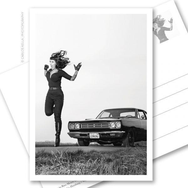 Postkarte Tura Satana Tribute. Ein postalischer Gruß im B-Movie-Style für US-Car- und Modern Pin-up Fans. Burlesque-Performer Lou on the Rocks und ein Plymouth Roadrunner HEMI von 1969 aus der Motoraver-Garage. Foto: Carlos Kella