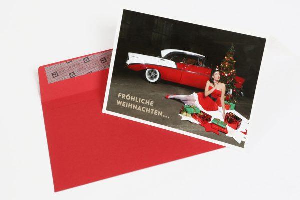 Weihnachts-Klappkarte mit rotem Umschlag. Hochglanz-Weihnachtskarte mit einem Cars & Girls Motiv im Format DIN A 6. Kalendermodel Sally und ein Chevrolet Bel Air von 1956