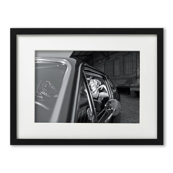 Foto-Print Oberhafen-Zyklus No. 01 auf Ilford S/W-Papier, gerahmt. Cars & Girls Fotografie von Carlos Kella im Format 21 x 31 cm mit Passepartout und Rahmen. Sophie Lee Galore und eine Chevy Nova , 1970 im Hamburger Oberhafen.