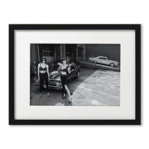 Foto-Print Oberhafen-Zyklus No. 02 auf Ilford S/W-Papier, gerahmt. Cars & Girls Fotografie von Carlos Kella im Format 21 x 31 cm mit Passepartout und Rahmen. Sophie Bolvary & Laura Desirée und eine Chevy Nova,1972 im Hamburger Oberhafen.