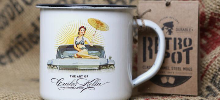 Der Carlos Kella Emaille-Becher im Retro-Look mit farbigem Motiv: Kalender-Covergirl Miss Stacey und ein Cadillac Sedan DeVille von 1959.